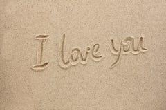 A palavra eu te amo escrita na areia Fotografia de Stock