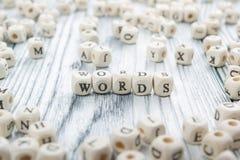Palavra feita com letra de madeira do bloco ao lado de uma pilha de Fotos de Stock Royalty Free