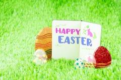 Palavra feliz da Páscoa no caderno Open na grama verde com colorido imagens de stock
