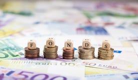 Palavra Fonds em pilhas da moeda, fundo do dinheiro Fotos de Stock Royalty Free