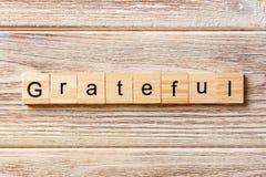 Palavra grata escrita no bloco de madeira Texto grato na tabela, conceito imagens de stock royalty free