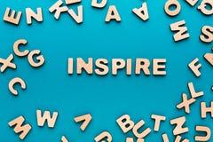 A palavra inspira no fundo azul Foto de Stock