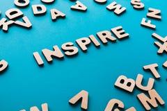 A palavra inspira no fundo azul Imagens de Stock Royalty Free