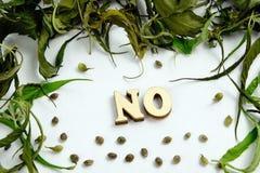 A palavra NENHUMA é apresentada de letras de madeira no centro do quadro das folhas secas e das grões do cannabis imagens de stock