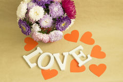 A palavra & o x22; love& x22; e um ramalhete das flores em um fundo do papel de embalagem marrom Fotografia de Stock