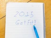 A palavra 2015 obtém o ajuste no caderno, pena no fundo de madeira Imagens de Stock Royalty Free