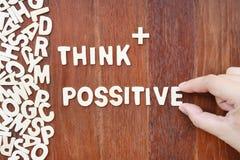 A palavra pensa o positivo feito com letras de madeira do bloco Fotos de Stock
