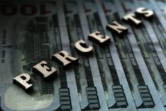 A palavra POR CENTO é alinhada com letras de madeira no fundo de contas de cem-dólar O conceito das transações financeiras fotografia de stock