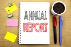 Palavra, redigindo o informe anual Conceito do negócio para analisar o desempenho escrito no fundo do papel de nota do bloco de n Imagens de Stock Royalty Free