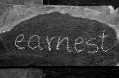A palavra SÉRIO escrito com giz na pedra preta Fotos de Stock