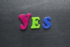 Palavra soletrada sim para fora usando ímãs coloridos do refrigerador Fotos de Stock Royalty Free