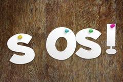 Palavra SOS cortada do papel Fotos de Stock Royalty Free