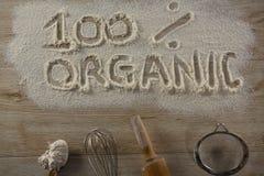 A palavra um orgânico de 100 por cento escrito na farinha polvilhada Fotografia de Stock Royalty Free