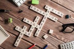 Palavras-chaves conceptuais na tabela de madeira com os elementos do jogo que fazem palavras cruzadas Imagens de Stock