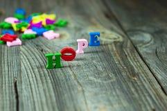 Palavras da esperança das letras de madeira pequenas em uma superfície cinzenta Imagem de Stock Royalty Free