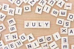 Palavras de julho com blocos de madeira Imagem de Stock
