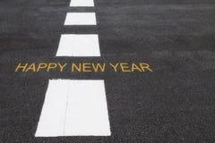 Palavras do ano novo feliz na estrada asfaltada Imagens de Stock