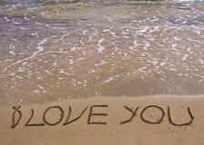Palavras EU TE AMO escritas na areia, com as ondas no fundo Fotografia de Stock Royalty Free