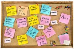 Palavras incorporadas escritas nas notas de papel em um quadro de mensagens da cortiça. Imagens de Stock