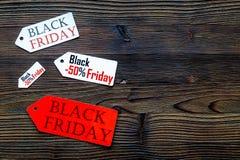 Palavras sexta-feira preta em etiquetas coloridas no copyspace de madeira escuro da opinião superior do fundo Foto de Stock