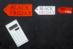 Palavras sexta-feira preta em etiquetas coloridas perto da calculadora no copyspace preto da opinião superior do fundo Fotografia de Stock