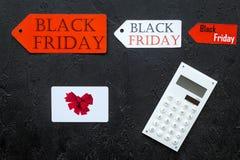 Palavras sexta-feira preta em etiquetas coloridas perto do cartão e da calculadora na opinião superior do fundo preto imagem de stock