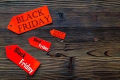 Palavras sexta-feira preta em etiquetas do vermelho no copyspace de madeira escuro da opinião superior do fundo Imagens de Stock Royalty Free