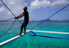 Landscape of tropical sea at sunny day. Palawan, Philippines - Apr 5, 2017. A man working on wooden boat at El Nido township in Palawan, Philippines. Palawan is stock images