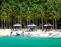 Landscape of tropical sea at sunny day. Palawan, Philippines - Apr 5, 2017. People sun-bathing on the beach with many plam trees in Palawan, Philippines. Palawan stock photography