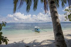 Palawan, the Philippines - 24 November 2018: turquoise sea lagoon and boats, tropical island landscape. Filippino wooden boat on white sand beach. Coco palm royalty free stock photos