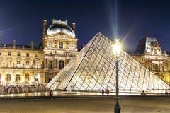 Palazzo del Louvre e piramidi alla notte, Parigi, Francia fotografia stock