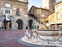 Palazzo della Ragione and Palazzo del Podesta. BERGAMO, ITALY - FEBRUARY 19, 2019: people near Palazzo della Ragione and Palazzo del Podesta on Piazza Vecchia stock photo