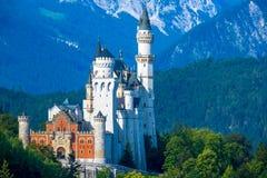 Palazzo il Neuschwanstein circondato dalle montagne boscose Fotografia Stock