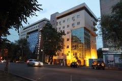 Palazzo multipiano di costruzione di sera della via moderno Fotografia Stock