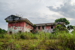 Palazzo rovinato circondato da verde fertile con il cielo drammatico Tracce della guerra civile in Robertsport, Liberia fotografia stock libera da diritti