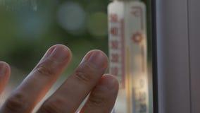 Palców mężczyźni dotykają okno który dołącza rtęć termometr pokazuje temperaturowego outside 32 stopnia, zbiory
