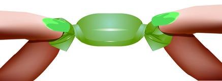 Palce trzyma cukierku A kobiety ` s rękę trzymają zielonego cukierek Fotografia Royalty Free