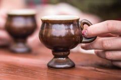 Palce trzymają filiżankę kawy na stole obrazy stock