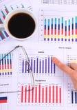 Palcowego seansu pieniężny wykres, szkła i filiżanka kawy, biznesowy pojęcie zdjęcie stock