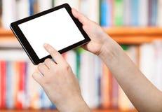 Palcowy dotyk pastylki komputer osobisty na przodzie książkowe półki Fotografia Stock