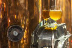 Pale ale in a brewery. Glass of pale ale beer standing on a piece of production brewing equipment Stock Photography