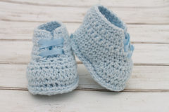 Pale Blue Baby Booties on wood background Royalty Free Stock Photos