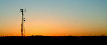 Pale Blue Cell Phone Tower Sunset. A cell phone tower silhouette in the sunset Stock Images