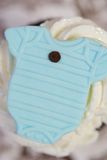 Pale Blue Onesie on Cup Cake. Baby Boy Shower Invitation Background with Pale Blue Onesie on Cup Cake Royalty Free Stock Photo
