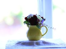 Small posy of spring flowers in a small, yellow jug on a windowsill. Pale blue, pink, burgundy and white flowers with green leaves in a small bouquet displayed royalty free stock photos