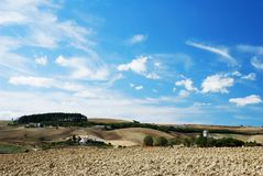 Pale blue and white. Sky over cultivated land and old church stock images