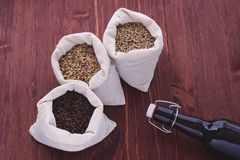 Pale, caramel, chocolate malt in a bags and bottle. Craft beer b. Rewing from grain barley malt in process. Ale or lager from pale or dark pilsner malt. wooden royalty free stock photos