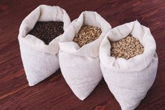 Pale, caramel, chocolate malt in a bags. Craft beer brewing from. Grain barley malt in process. Ale or lager from pale or dark pilsner malt. wooden background Royalty Free Stock Photos