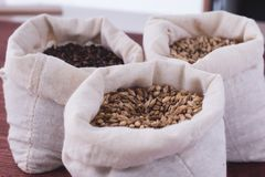 Pale, caramel, chocolate malt in a bags. Craft beer brewing from. Grain barley malt in process. Ale or lager from pale or dark pilsner malt. wooden background Stock Photos