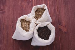 Pale, caramel, chocolate malt in a bags. Craft beer brewing from. Grain barley malt in process. Ale or lager from pale or dark pilsner malt. wooden background Stock Images